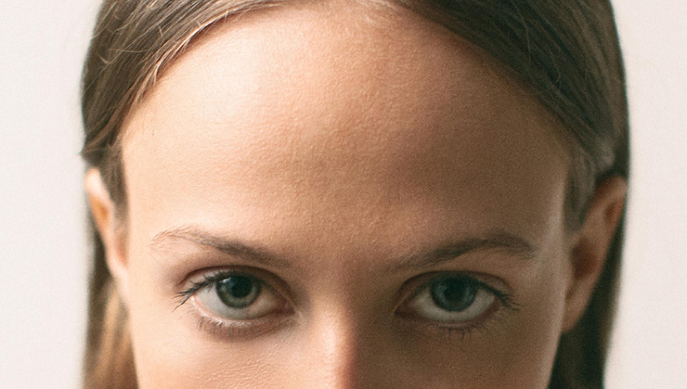 a zoomed in image of a young woman's forehead and eyes