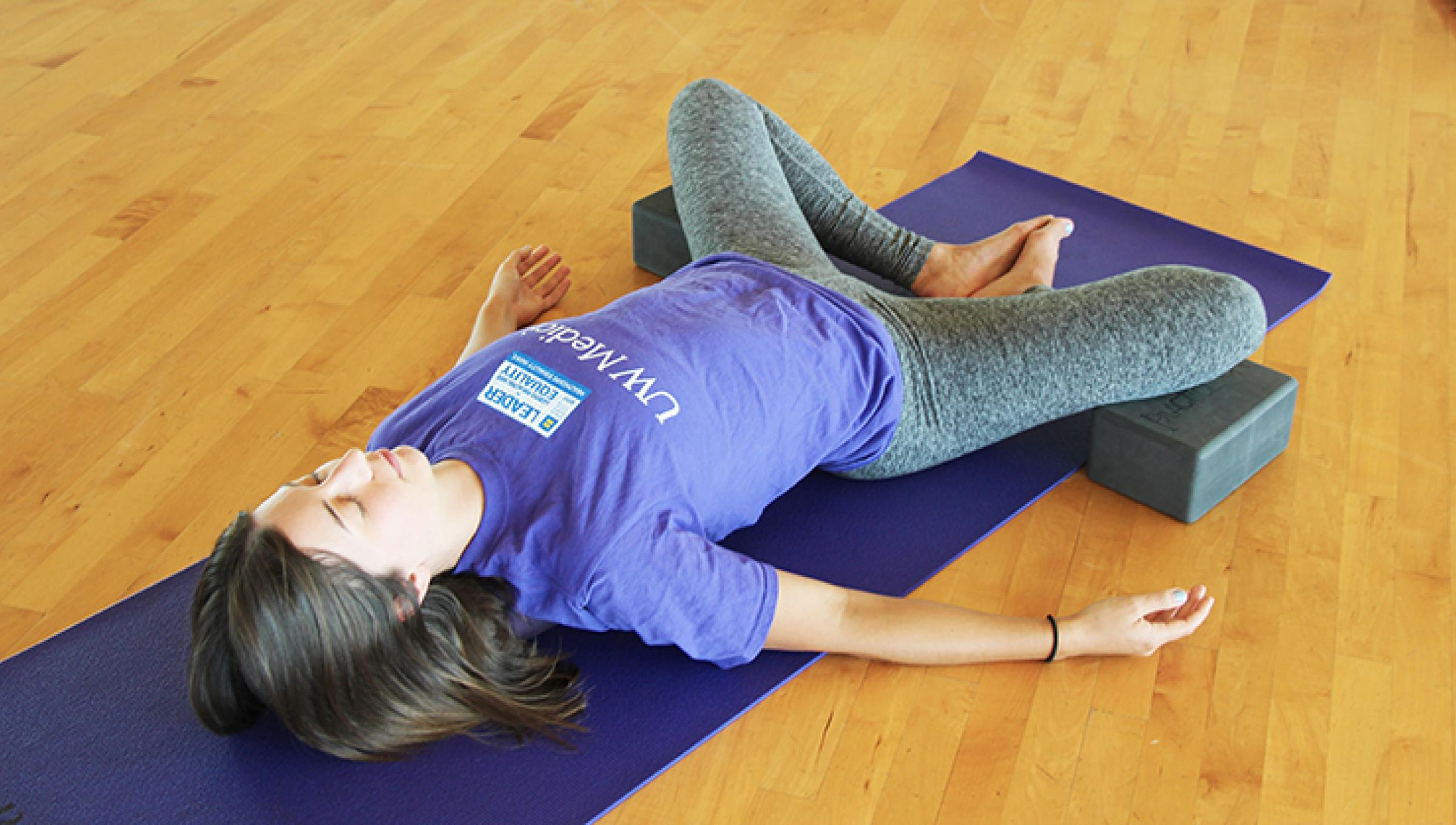 a woman doing the yoga pose called supported reclining bound angle pose