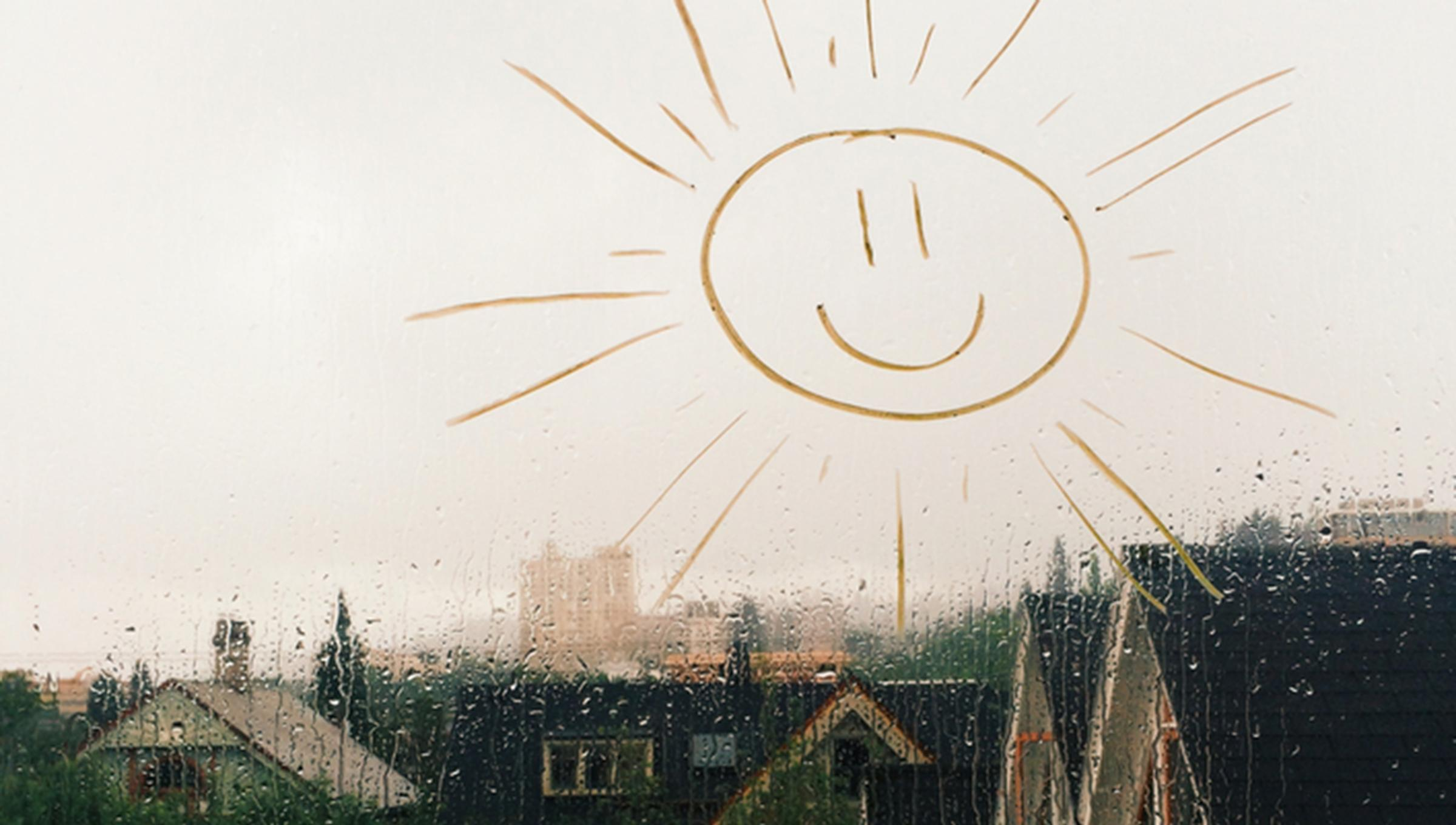child's sunshine drawing on a rain covered window