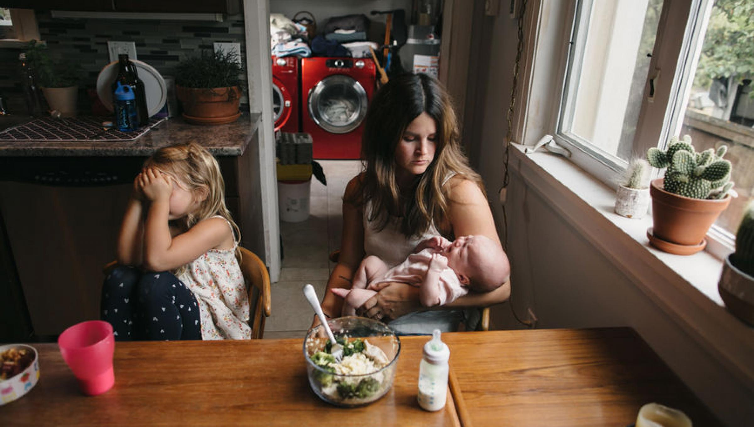 Exhausted mama holds baby at the kitchen table