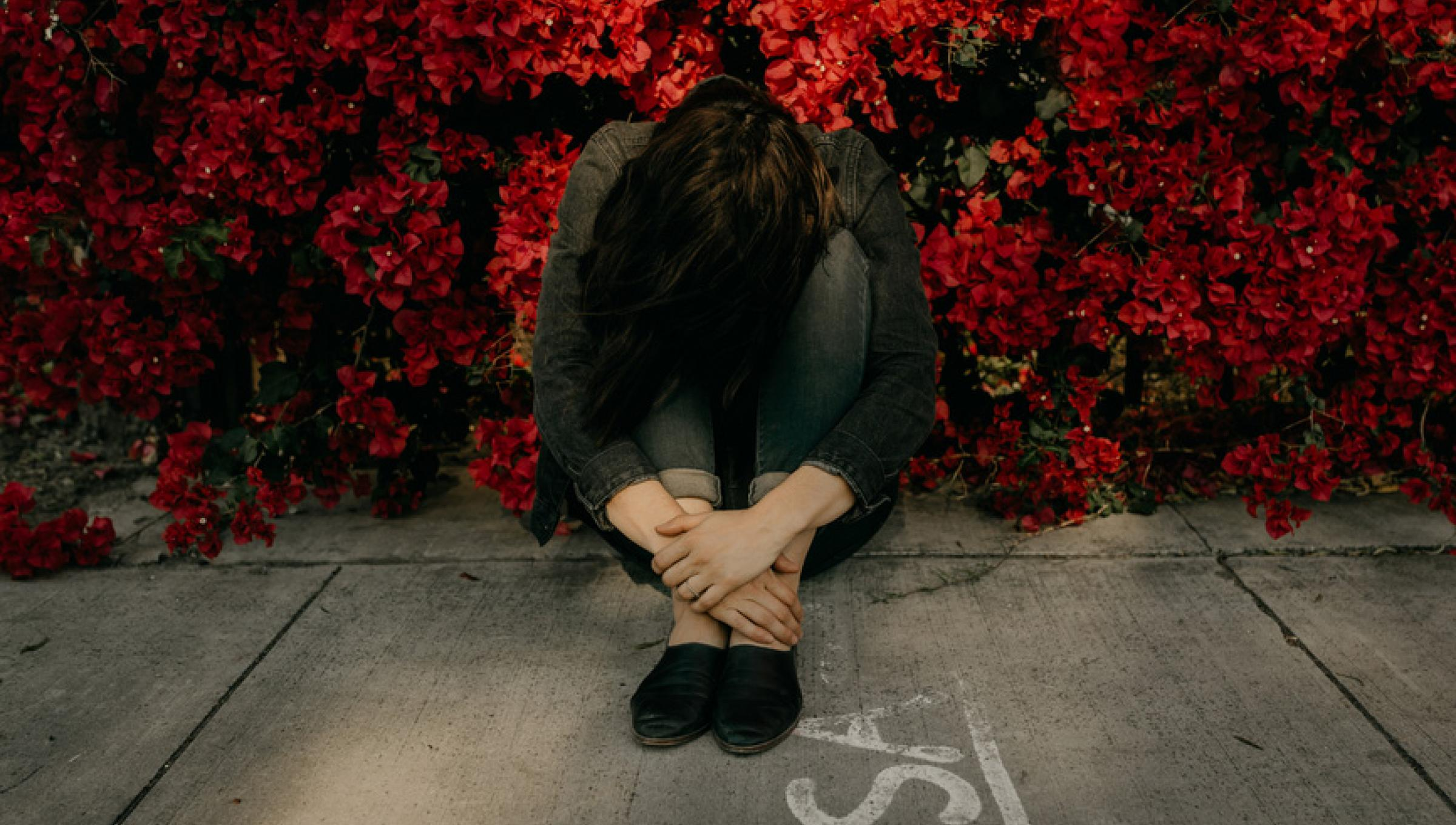 Woman with head down sitting amidst red flowers
