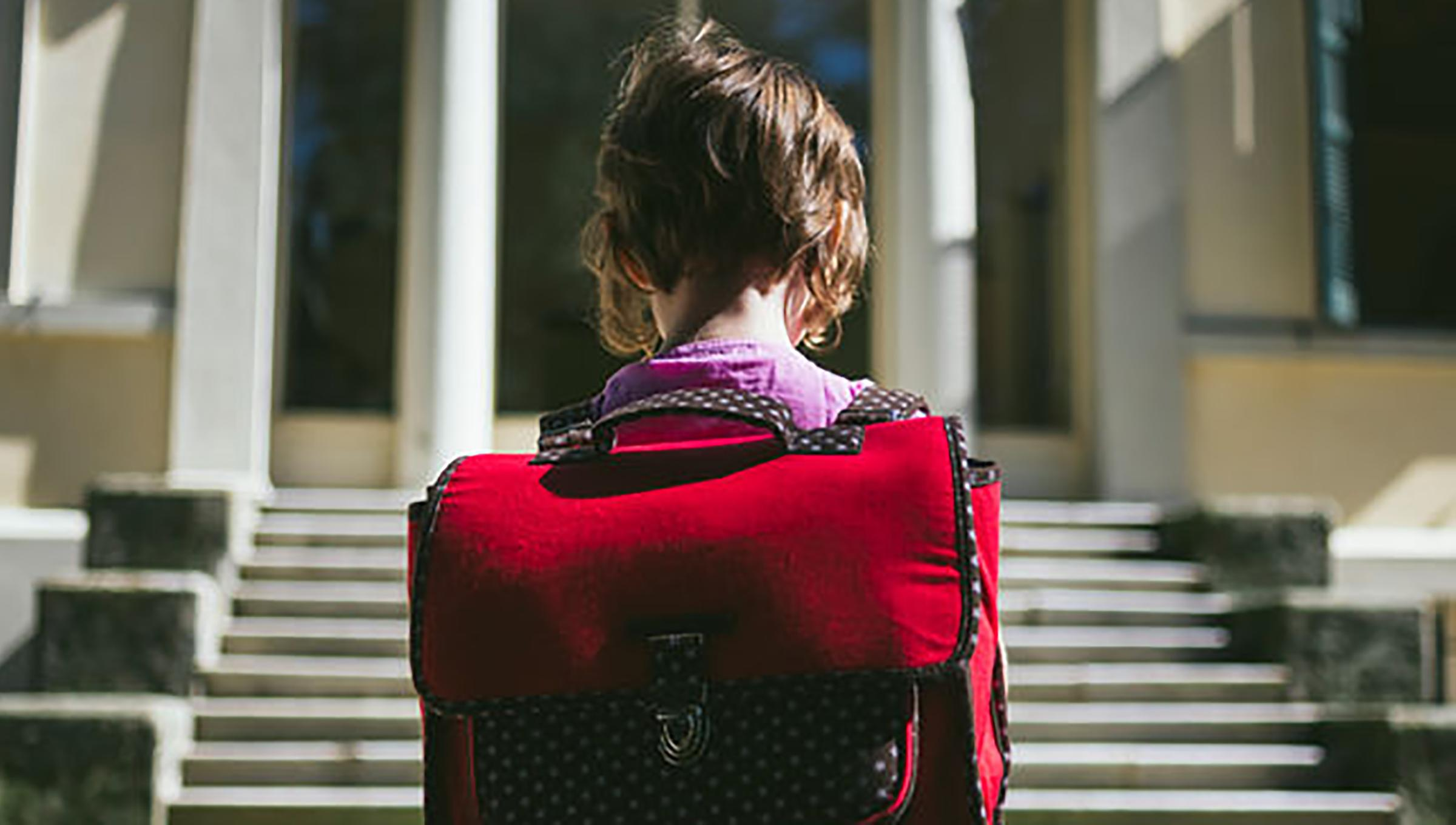 741bfd8a6d1f Child with red backpack on first day of school