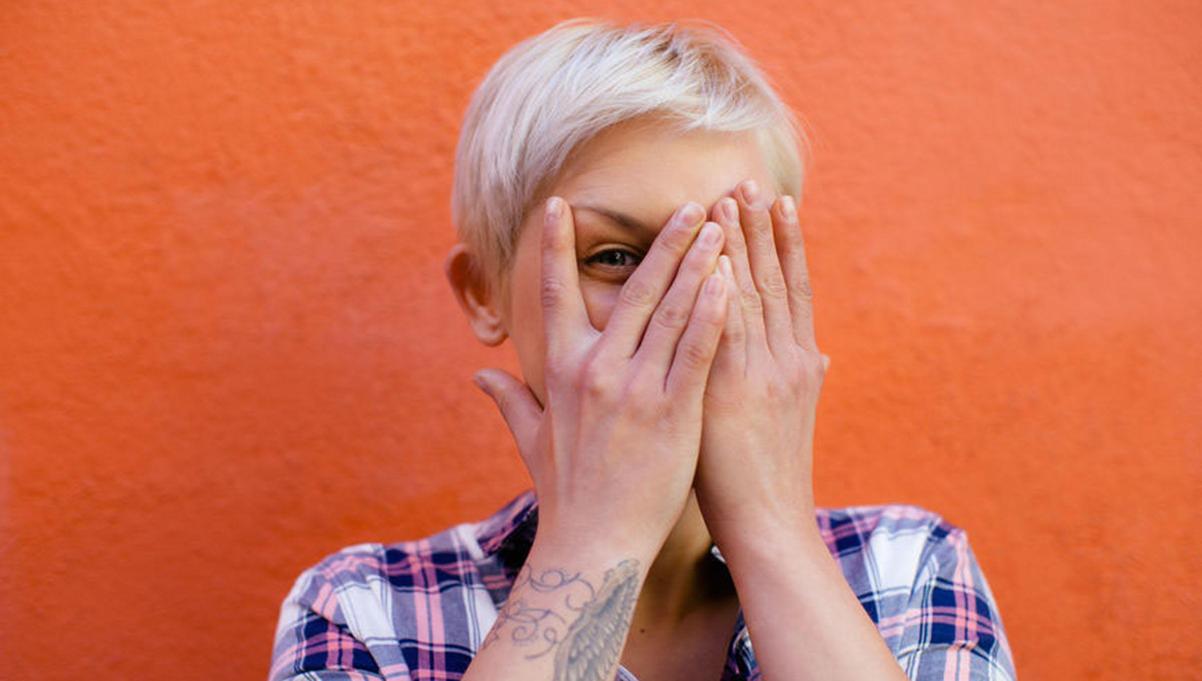Blonde woman covering one eye with hands