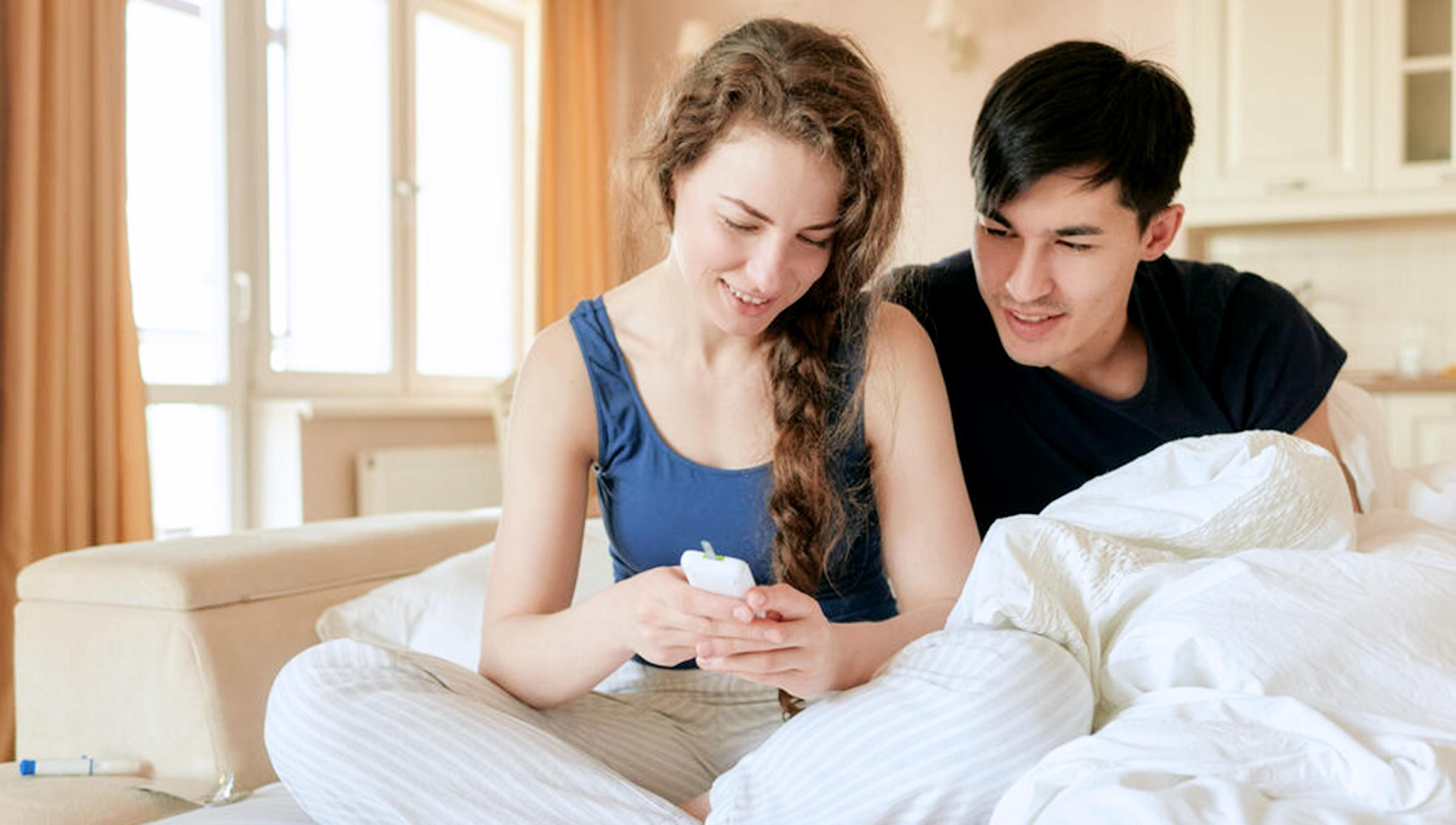 A man and woman sit in bed looking at the woman's glucose monitor.