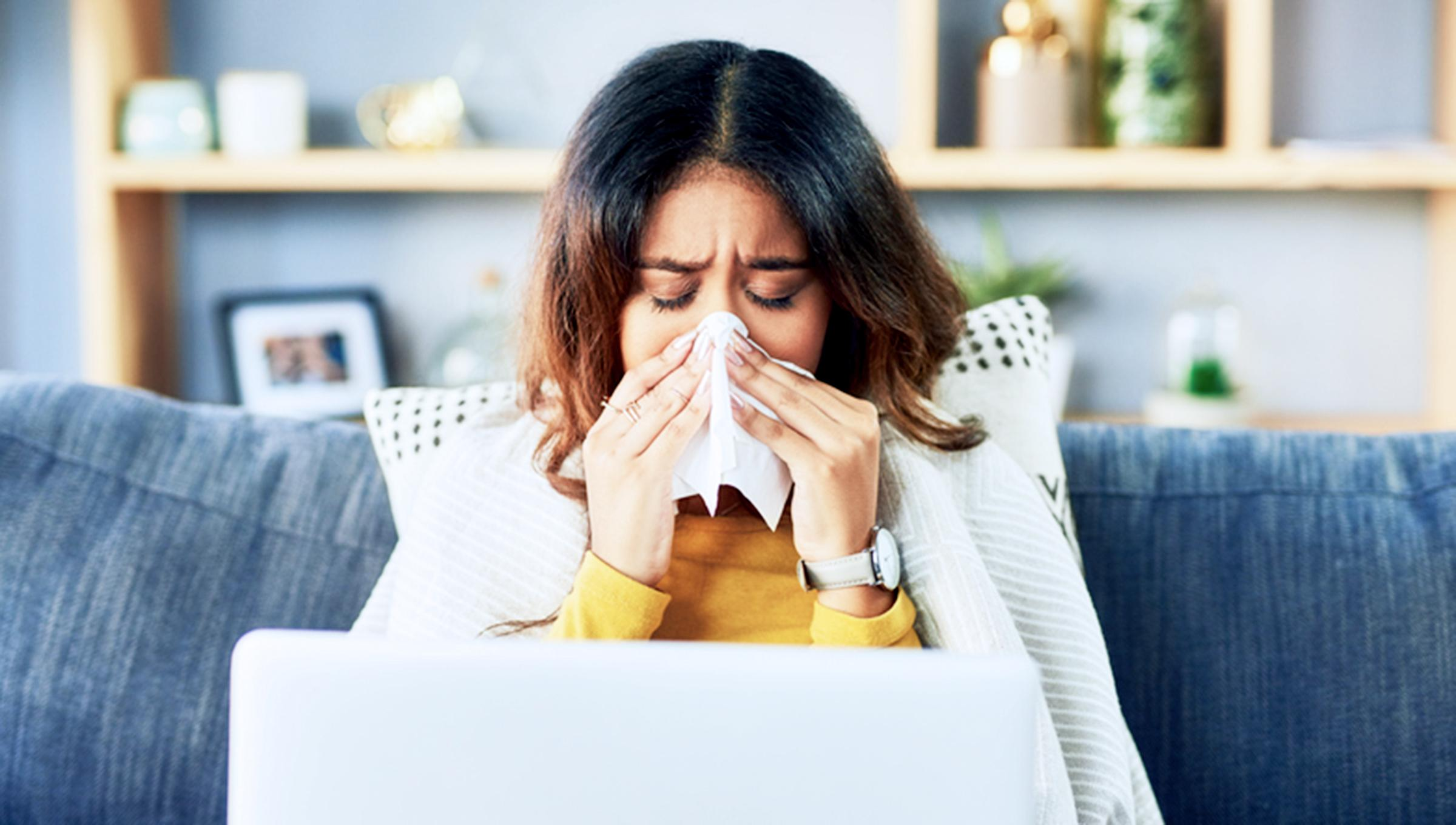 A woman sitting on her couch wrapped in a blanket blows her nose.