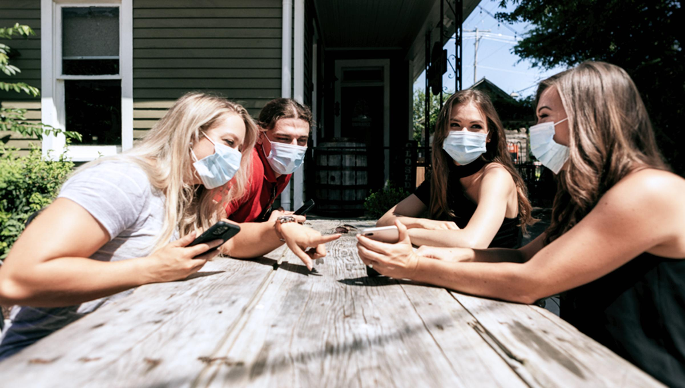 Friends around picnic table with masks on