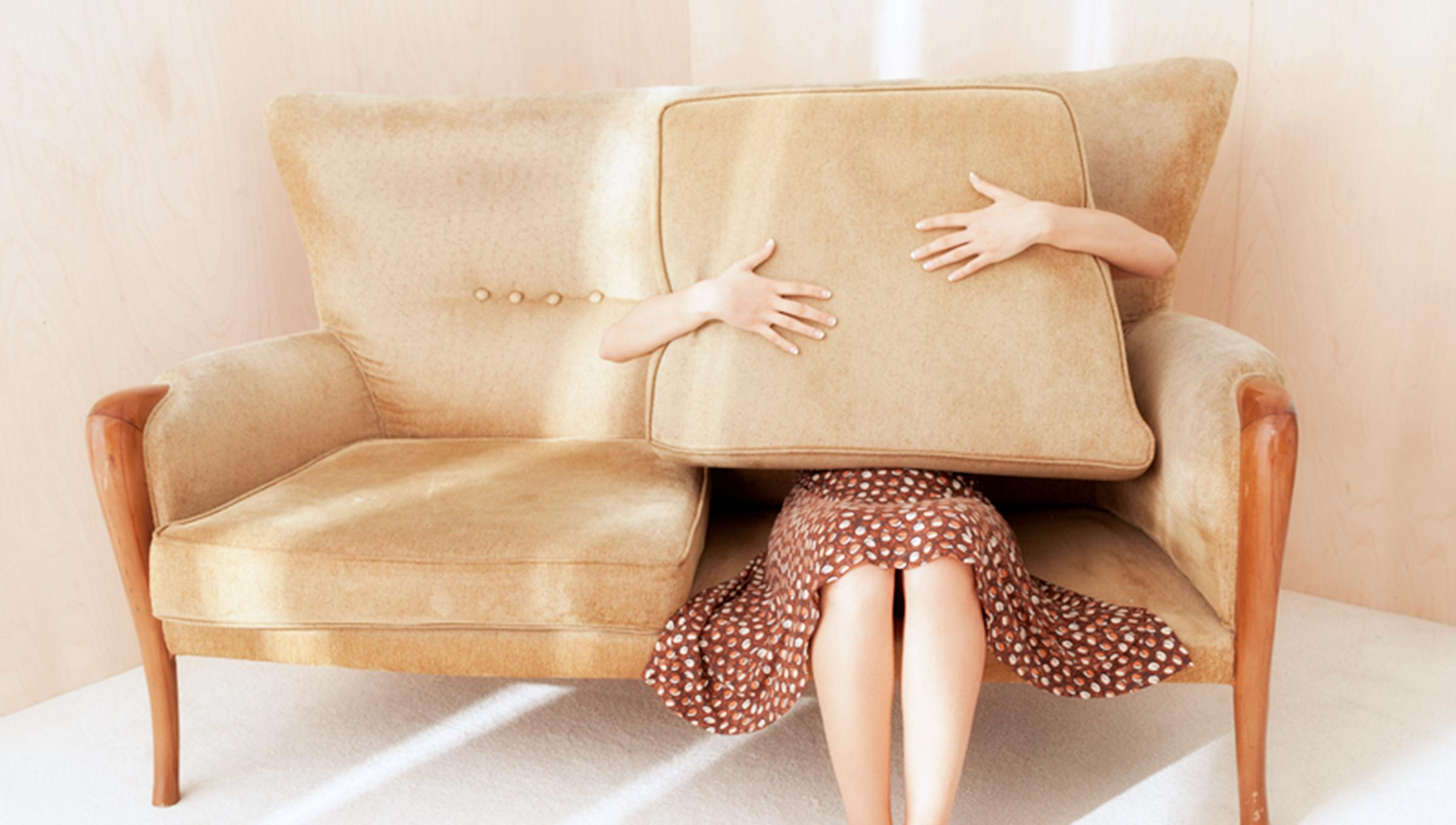 A woman sits on a couch holding a pillow over her upper body and face.