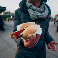 woman holding a hot dog while traveling