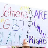 An activists's sign at a protest that supports women's rights, LGBTQ rights and black rights.