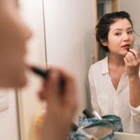 Woman-doing-makeup-in-mirror