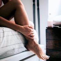 woman sitting on side of bed holding leg