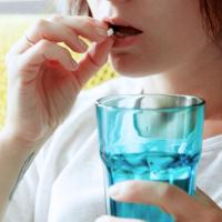 A woman holds a glass of water while taking a pill.