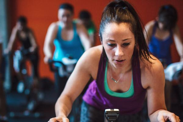 young woman sweating while participating in an indoor cycling class