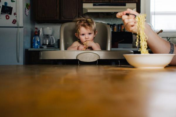 Toddler in high chair at table with spaghetti on head