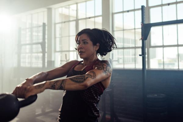 a woman swinging a kettle bell in a gym