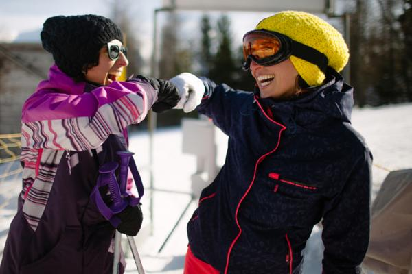 A skier and a snowboarder are smiling and fist bumping as they wait in line to get on the chairlift.