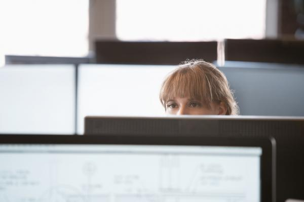 Woman staring over office cube wall