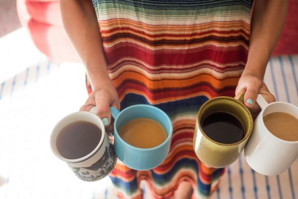 Young woman in dress holding four eccentric mugs full of coffee in a home