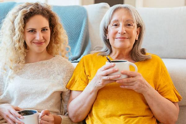 Mom and daughter sipping coffee against couch