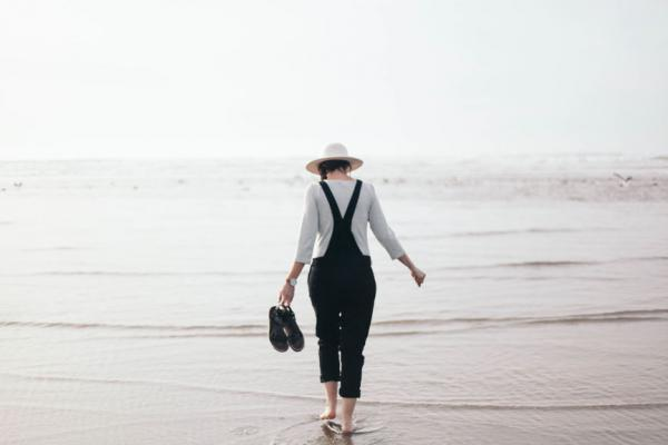 Woman in hat walks in shallow ocean water