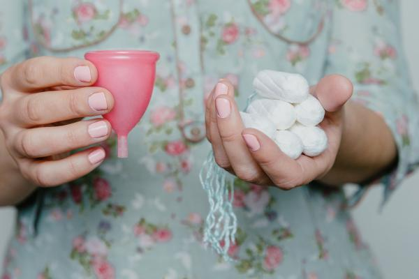 Close up of a woman's hands holding a menstrual cup and tampons