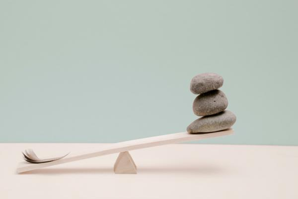 an unbalanced scale with a feather and rocks on it
