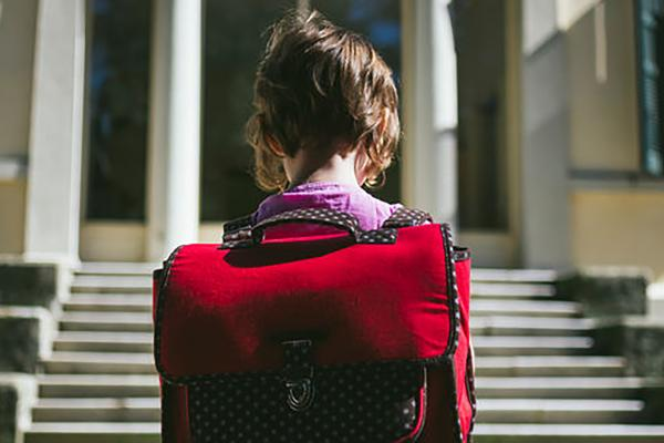 Child with red backpack on first day of school
