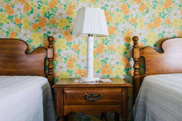 Twin beds against wall with vintage wallpaper