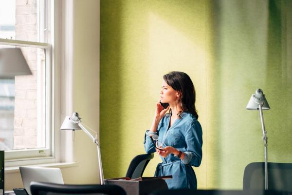Woman in green office on telephone