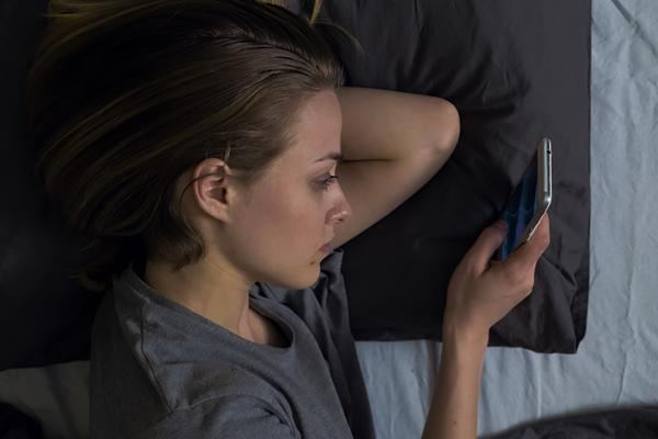 a young woman lying in bed looking at her phone