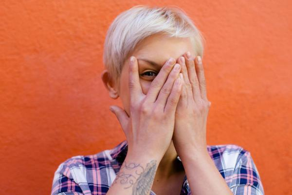 Blonde woman covering one eye with her hands