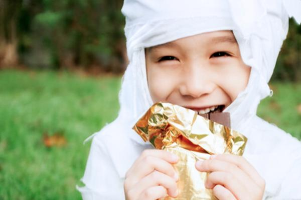 A young boy dressed as a mummy eats a bar of chocolate.