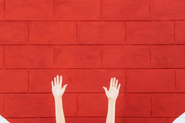 Hands reaching up in front of a brick wall painted red.