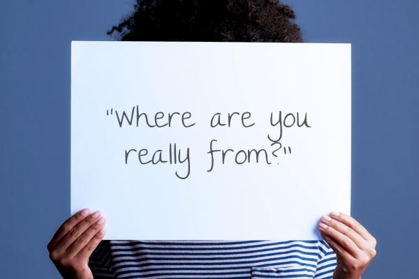 A black woman holding a sign with a microaggression written on it that says: Where are you really from?.