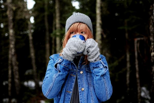 A woman wearing cold weather clothes sips a hot drink standing out in the woods.