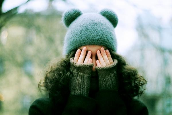 A person with long hair wearing a winter hat covers her face with her hands.