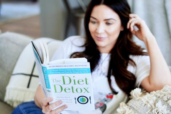 A woman sitting on the couch reading a diet book.