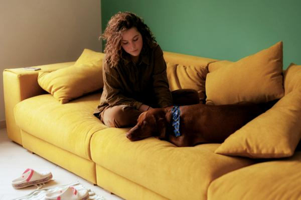 woman-sitting-on-yellow-couch