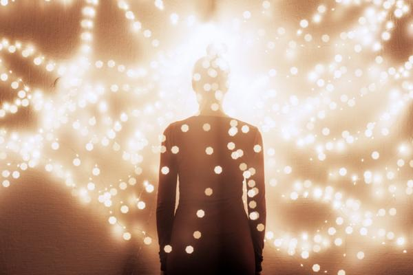 A woman's silhouette stands surrounded by glowing string lights.