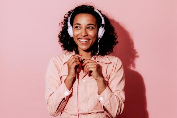 Woman listening to headphones with pink backdrop