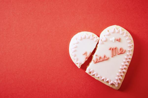 "A heart-shaped cookie that says ""Kiss Me"" but is broken, on a red background."