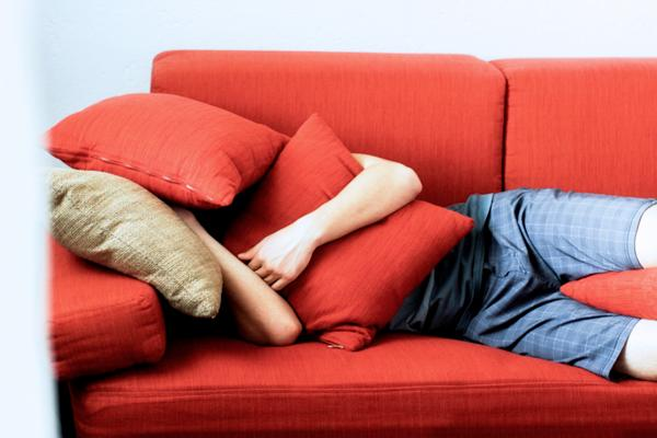 man-hiding-face-on-couch