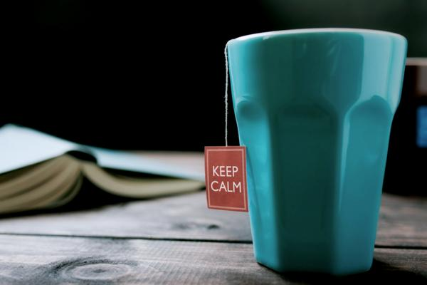 A blue mug on a wooden table with a teabag tag hanging out of it that says Keep Calm.