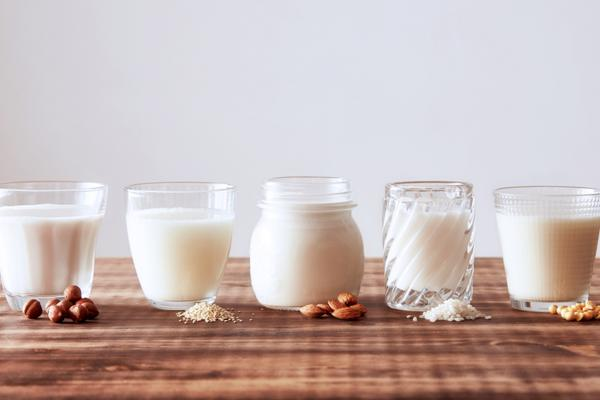 A lineup of non-dairy milk alternatives in glasses.
