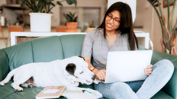 Woman on her computer cuddling with her dog