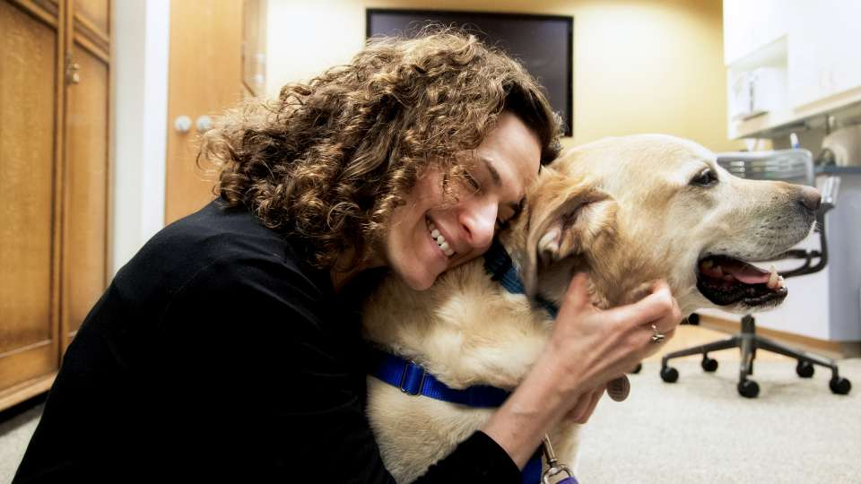 A woman hugs a dog during a pet therapy session.