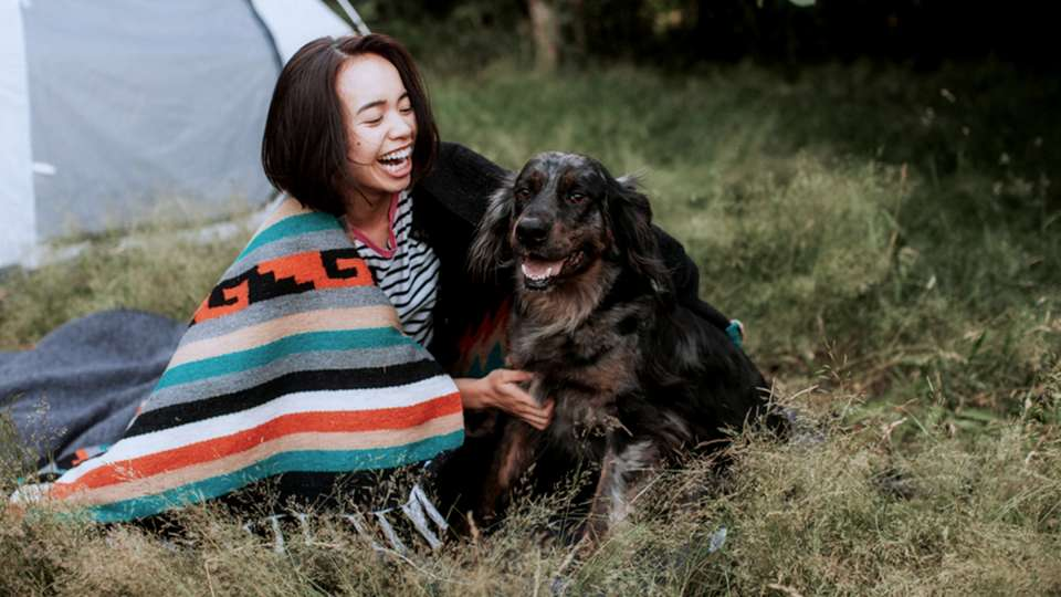 Woman cuddles her dog while camping outside