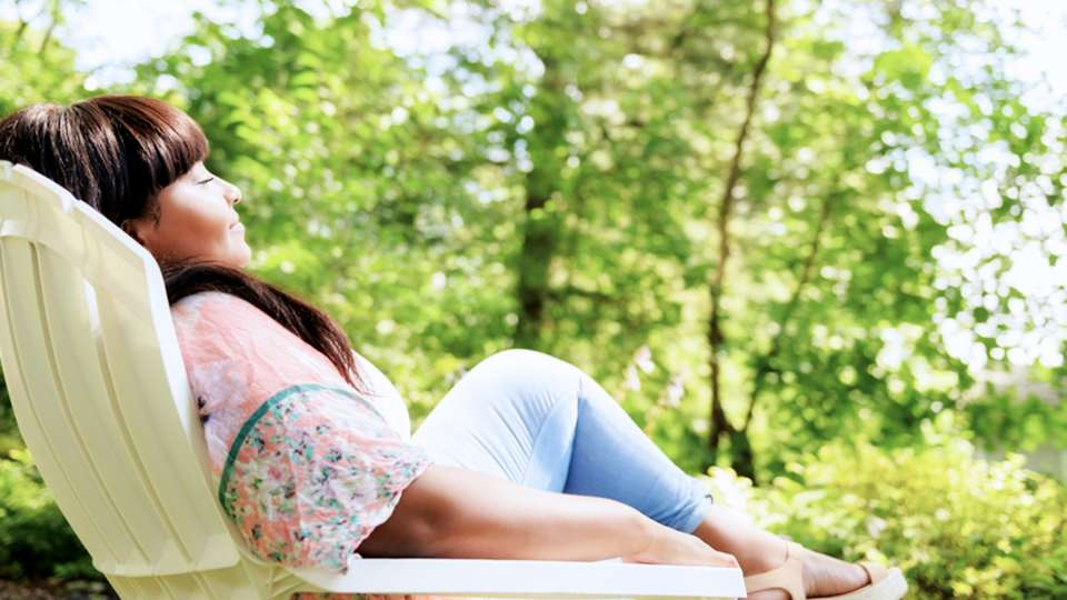 Woman relaxes on a comfortable chair outside