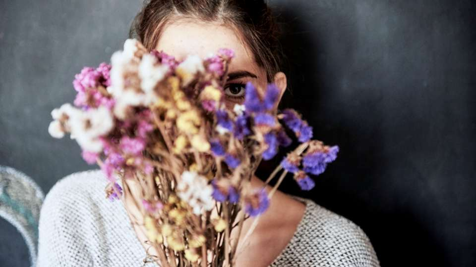 A woman holds dried flowers up to partially cover her face.