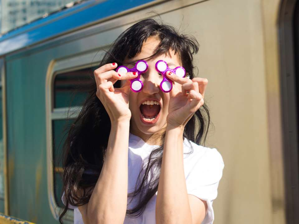 a young woman holding fidget spinners over her eyes